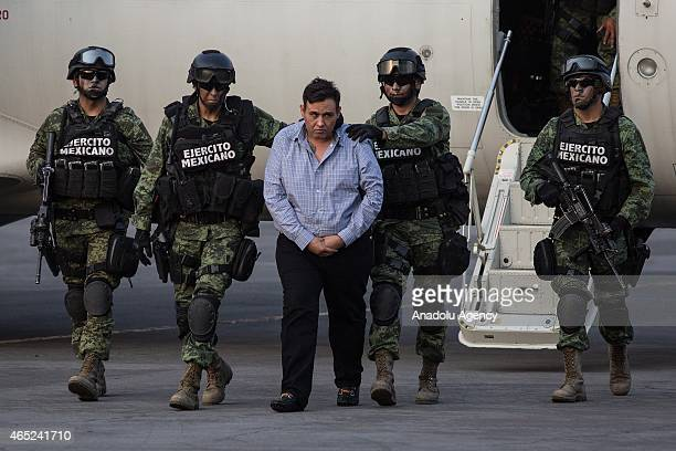 Soldiers escort a man who authorities identified as Omar Trevino Morales alias Z42 leader of the criminal group Los Zetas at the Attorney General...
