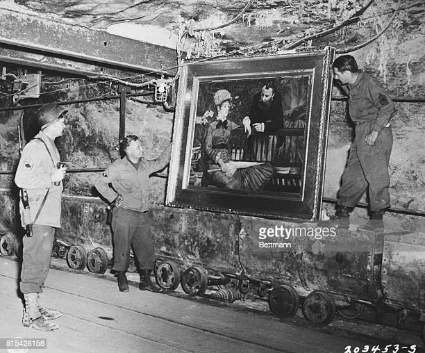 "Soldiers examine ""Wintergarden"", famous painting by the French impressionist Edouard Manet, found in collection of Reichbank wealth, SS loot, and art..."