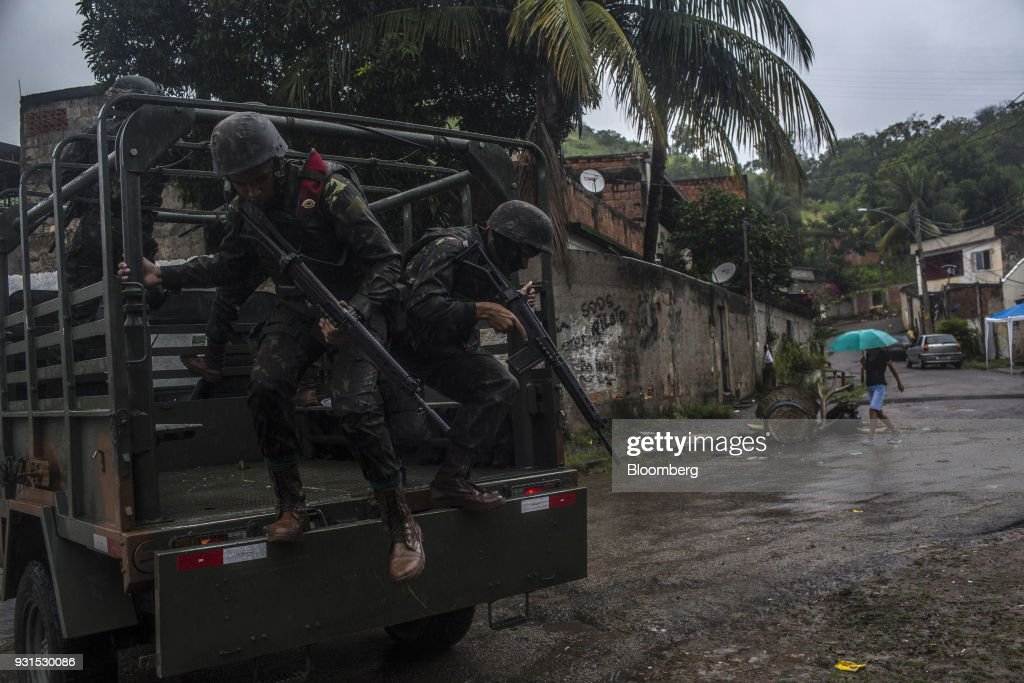 Soldiers exit a vehicle to patrol streets in the Vila Kennedy neighborhood in Rio de Janeiro, Brazil, on Thursday, March 8, 2018. As public safety remains a top concern for Brazilian voters, President Michel Temer gave the military control of security measures in Rio in an effort increase approval ratings ahead of the country's elections in October. Photographer: Dado Galdieri/Bloomberg via Getty Images