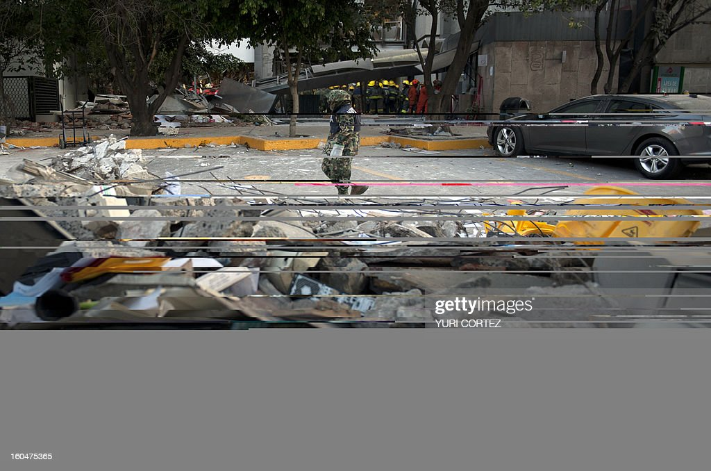 Soldiers, Federal policemen and firefighter remove debris looking for victims of the headquarters of state-owned Mexican oil giant Pemex in Mexico City on February 1, 2013, following a blast inside the building. An explosion rocked the skyscraper, leaving up to now 32 dead and 100 injured, as a plume of black smoke billowed from the 54-floor tower, according to official sources.