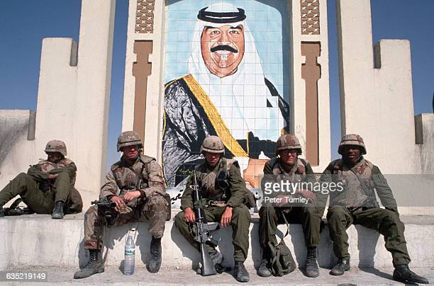 US Soldiers fighting in the Gulf War sit under a portrait of Iraqi leader Saddam Hussein at the border of Iraq and Kuwait | Location Border of Iraq...