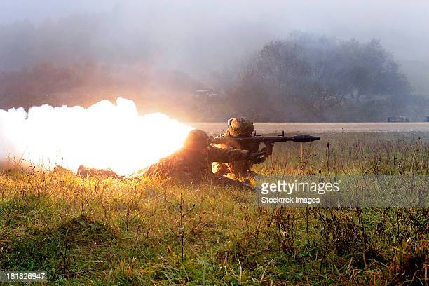 Soldiers fire a rocket propelled grenade at opposing forces.