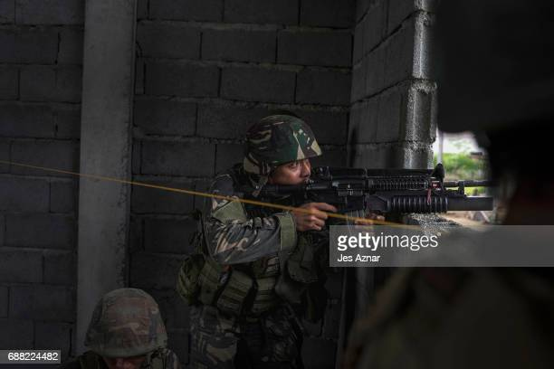 Soldiers fire at enemy positions while they try to clear the city of armed militants one street at a time on May 25 2017 in Marawi city southern...