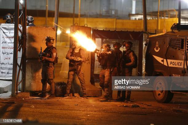 Soldiers fire tear gas at Palestinian demonstrators during an anti-Israel protest over tension in Jerusalem, at the Qalandiya checkpoint between...
