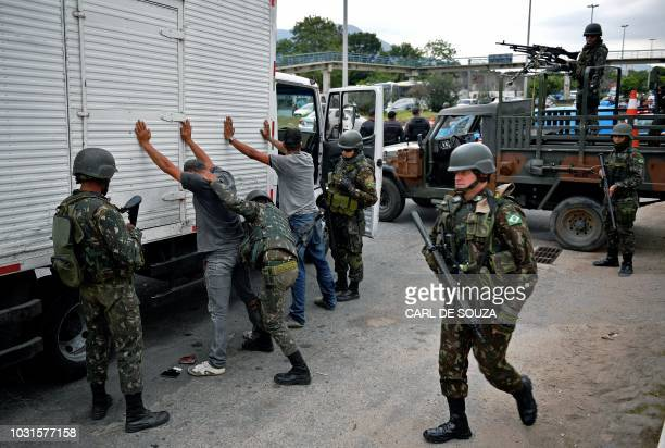 Soldiers frisk the drivers of a truck during an operation to reduce thefts in cargos in Rio de Janeiro Brazil on September 11 2018 Security officials...