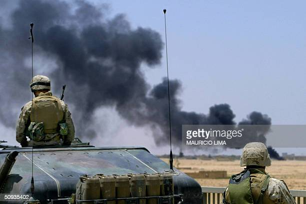 US soldiers from 2nd Batallion 1st Marines stands on a bridge over a highway inspecting a plume of black smoke on the outskirts of the Sunni Muslim...