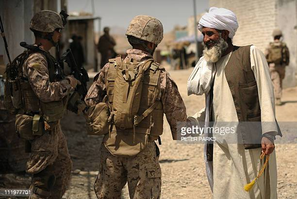 US soldiers from 3rd Battalion 2nd Marine Regimental Combat Team 8 talk to an Afgan elder in the town of Musa Qala in Helmand province in southern...