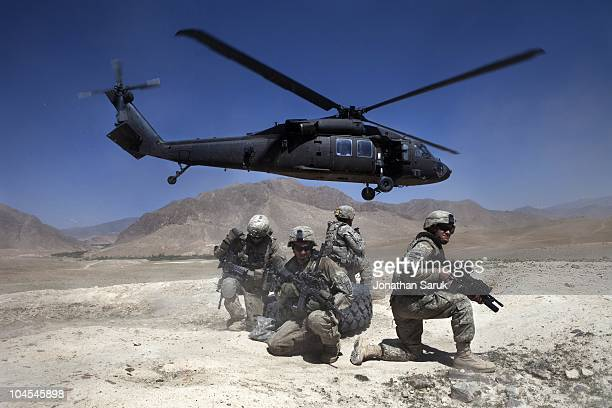 US soldiers from 3rd Brigade 10th Mountain Division take cover as a UH60 Blackhawk helicopter takes off after dropping off a replacement tire for a...