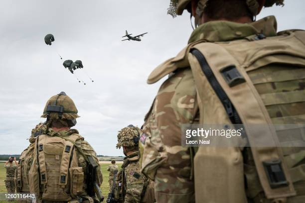 Soldiers from 4 Brigade look on as an RAF Hercules transport plane makes an airdrop during a military exercise on Salisbury Plains on July 23, 2020...