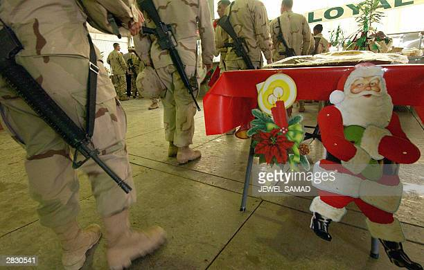 US soldiers from 4th Infantry Division queue up for their meal next of a cartoon Santa Claus at their base in Tikrit 180 Kilometers north of Iraqi...