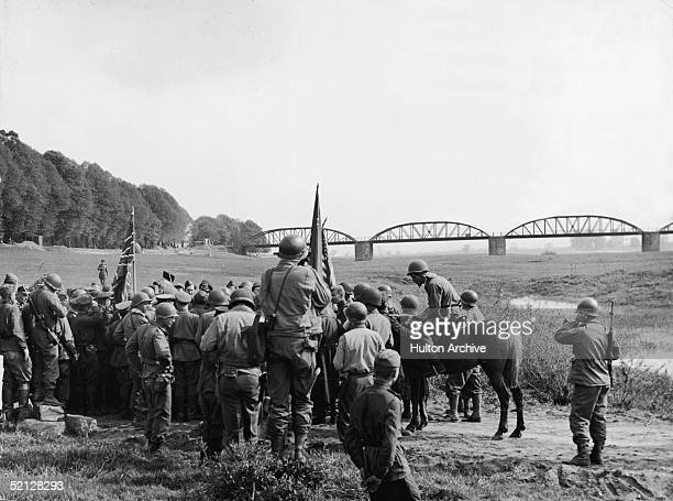 Soldiers from both armies gather around as American and Russian generals and officers meet on the banks of the Elbe River Torgau Germany April 26 1945