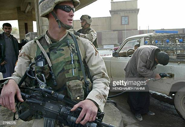 Soldiers from the 101 Airborne Division keep guard while inspecting a gas station in the town of Mosul some 400 kms north of Baghdad after a driveby...