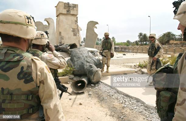 US soldiers from the 101st Airbone shoot a souvenir picture in front of a statue of toppled Iraqi leader Saddam Hussein lying on the ground after...