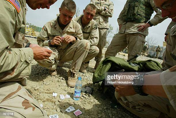 US soldiers from the 101st Airborne Battalion play cards after they disembarked from a Chinook helicopter at Bagram air base April 6 2002 in...