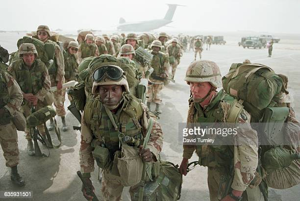 Soldiers from the 101st Airborne Division board a C130 transport plane during the Gulf War