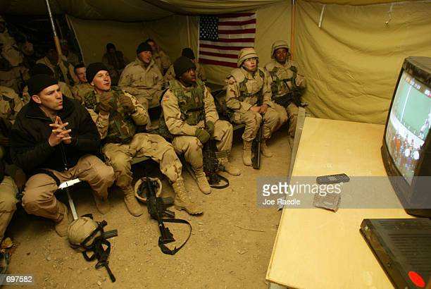 S soldiers from the 101st Airborne watch as the St Louis Rams and the New England Patriots play Super Bowl XXXVI February 3 2002 while stationed at...