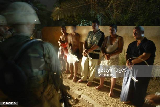 Soldiers from the 141st Field Artillery Brigade guard arrested Saad Taha Mussa al-Tikriti a former member of Uday Saddam Hussein's securitry...