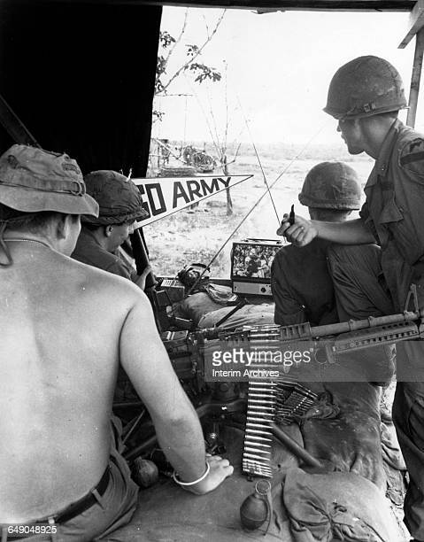 Soldiers from the 1st Air Cavalry gather around a television to take in an Army football game at Basecamp Phuoc Vinh as televised by American Forces...