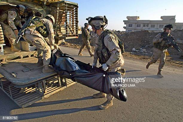 S soldiers from the 1st Battalion 24th Infantry Regiment evacuate a dead body lying on the street which they suspect is an Iraqi young man murdered...