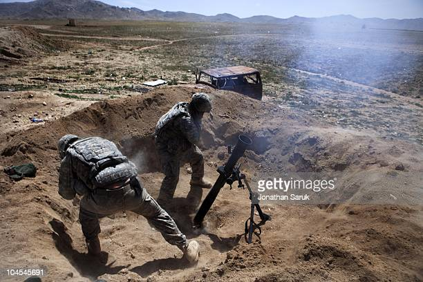 US soldiers from the 3rd Brigade 10th Mountain Division return mortar fire during an insurgent attack at the Jaghatu District Center May 12 2009 in...