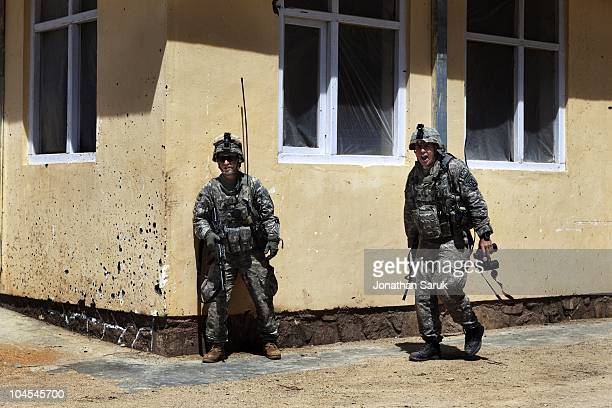 US soldiers from the 3rd Brigade 10th Mountain Division take cover from gunfire during an insurgent attack at the Jaghatu District Center May 12 2009...