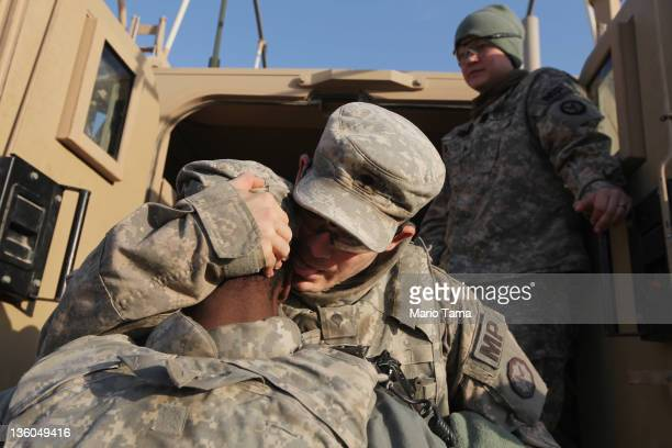 Soldiers from the 3rd Brigade 1st Cavalry Division hug while preparing to depart in the last convoy from Iraq at Camp Adder now known as Imam Ali...