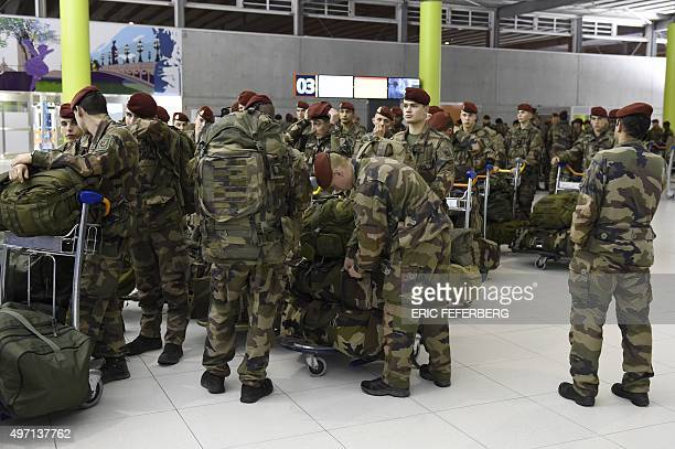 Soldiers from the 3rd Marine Infantry Parachute Regiment of Carcassonne pick up their luggage upon their arrival at Paris' Charles de Gaulle airport...