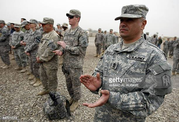 US soldiers from the 4th Infantry Division clap during a handing over ceremony to the 1st Cavalry Division held at Camp Victory which adjoins Baghdad...