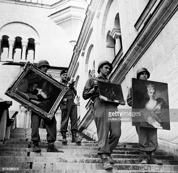 Soldiers from the 7th US Army carry three priceless artworks down the steps of Meunschwanstein Castle where hoards of European art treasures, stolen...