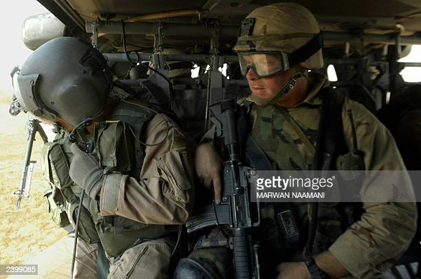 Soldiers from the 82nd airborne division in a Blackhawk helicopter prepare to land during a mission in southern Baghdad, 10 August 2003, to pick-up...