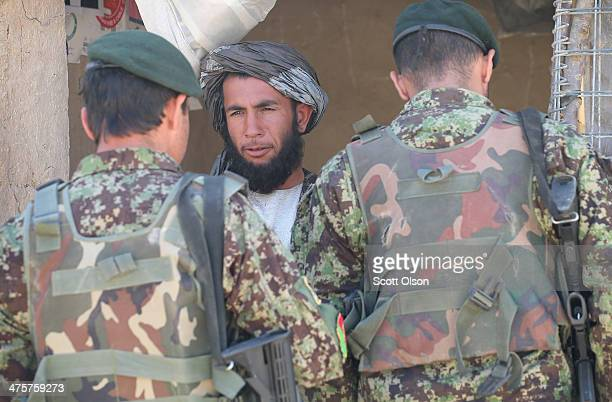 Soldiers from the Afghan National Army question a store owner during a joint patrol through a village with the US Army's 4th squadron 2d Cavalry...