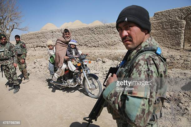 Soldiers from the Afghan National Army stop and check residents during a joint patrol through their village with the U.S. Army's 4th squadron 2d...