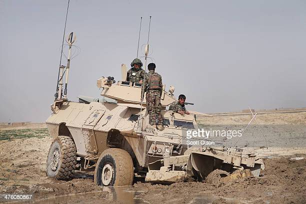Soldiers from the Afghan National Army try to free their vehicle after it got stuck in mud during a joint patrol with the U.S. Army's 4th squadron 2d...
