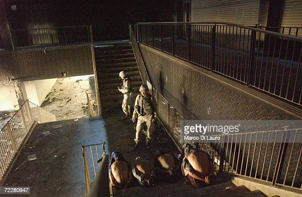 S soldiers from the Alfa Company 26 Infantry 1st Platoon 1st Squad Bravo Team detain looters at a government building on July 9 2003 in Baghdad Iraq...