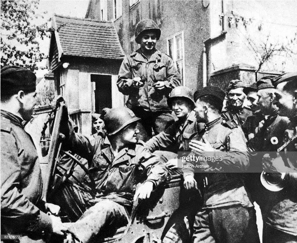 Soldiers from the American and Russian Armies gather around a jeep and chat and laugh, Torgau, Germany, April 28, 1945.