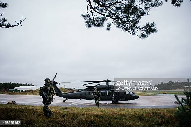 Soldiers from the Defence Forces of Ireland walk near a Blackhawk helicopter at Hagshult Airbase part of the Forward Operation Base of the NBG about...