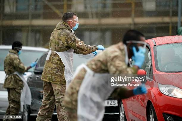 Soldiers from the Duke of Lancaster's Regiment, instruct people arriving at a 'pop-up' mobile Covid-19 testing centre on April 29, 2020 in...