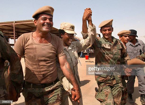 """Soldiers from the first battalion of the New Iraqi Army dance """"choby"""" style with U.S. Army 319th Military Public Affairs Division Specialist Briana..."""