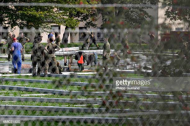 Soldiers from the german Bundeswehr build an emergency shelter for migrants on the campus of the Bundeswehr university on September 13 2015 in Munich...