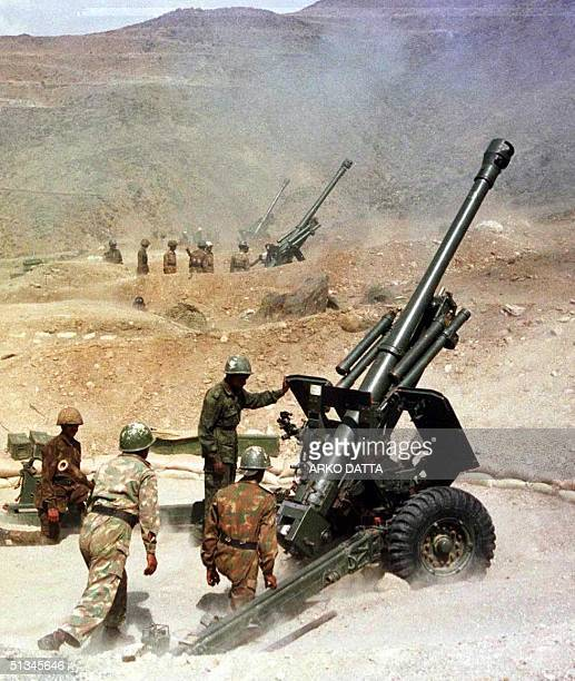 Soldiers from the Indian army fire their 105mm guns 31 May 1999 from their outpost near Kargil towards the IndiaPakistan border in Kashmir India...
