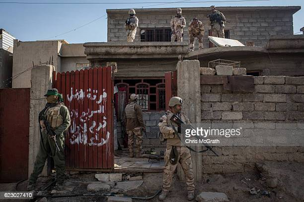 Soldiers from the Iraqi Army Armoured Ninth Division secure a house on a street just behind the frontline in the Intisar neighbourhood on November 13...