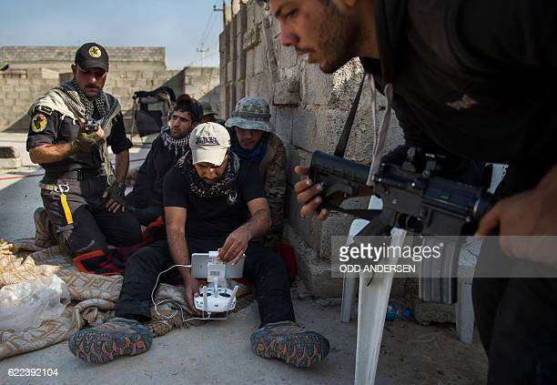 Soldiers from the Iraqi Special Forces 2nd division look at the remote control of a drone used to look for hostile positions while engaging Islamic...