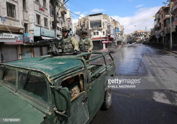 Soldiers from the Jordanian army patrol atop a military vehicle on a street in capital Amman during a nationawide curfew imposed by the authorities...