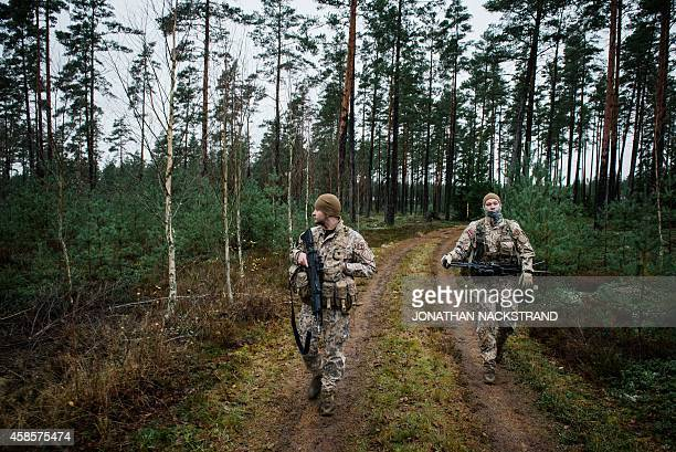 Soldiers from the Latvian National Armed Forces part of the NBG Quick Response Force patrol at Hagshult Airbase part of the Forward Operation Base of...