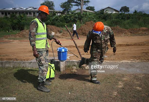 Soldiers from the Liberian Army's 1st Engineer Company disinfect their boots and hands before entering the construction site of an Ebola treatment...