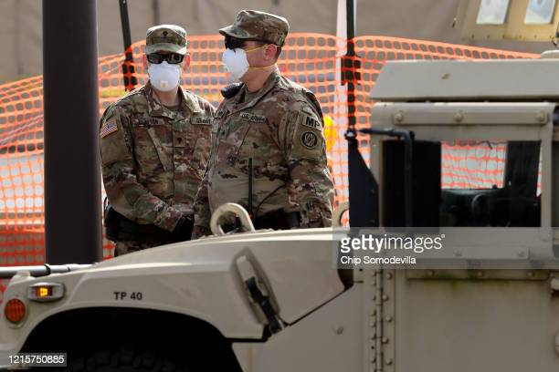 Soldiers from the Maryland National Guard stand guard at a site they build for screening people for the coronavirus in a parking lot at FedEx Field...