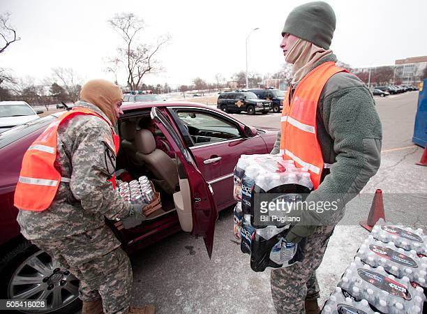 Soldiers from the Michigan Army National Guard Flint hand out bottled water at a fire station January 17 2016 in Flint Michigan US President Barack...