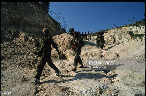 Soldiers from the Patriotic Front of Rwanda walk down a hilly path June 3 1994 in Rwanda They are preparing for the final offensive towards Kabyagi...
