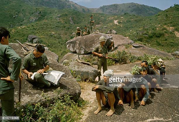 Soldiers from the Republic of Korea serving in the Vietnam War with a group of captured Vietcong prisoners | Location north of Bong Sen Vietnam