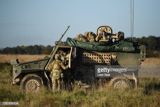 Soldiers from the Royal Anglian Regiment discuss their strategy as they approach the location of a reported improvised explosive device during their...